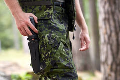 Close up of soldier or hunter with knife in forest stock image