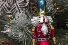 Hanging Christmas ornaments on tree. Close up of soldier nutcracker ornament hanging on frosted pine tree Christmas tree Stock Image
