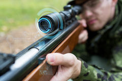 Close up of soldier or sniper with gun in forest Royalty Free Stock Image