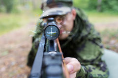 Close up of soldier or sniper with gun in forest Stock Photography