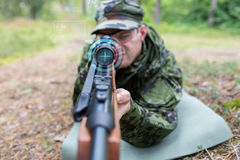 Close up of soldier or sniper with gun in forest Stock Image