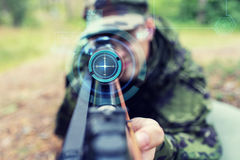 Close up of soldier or sniper with gun in forest Royalty Free Stock Photo