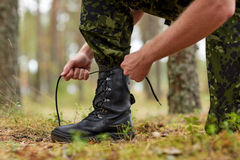 Close up of soldier tying bootlaces in forest. War, hiking, army and people concept - close up of soldier boots and hands tying bootlaces in forest stock image