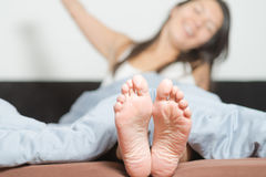 Close up of the soles of female feet. Close up of the cute crinkled soles of female feet belonging to a smiling playful woman relaxing in her bed with focus to Royalty Free Stock Photo