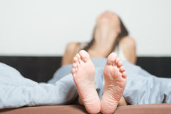 Close up of the soles of female feet. Close up of the cute crinkled soles of female feet belonging to a smiling playful woman relaxing in her bed with focus to Royalty Free Stock Photos
