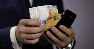 Close-up of a solid businessman pulls out the euro and Swiss francs from his wallet. stock video footage