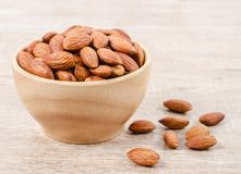 Close up some almonds in bowl. On wooden background Stock Photo