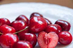 The Red cherries in plate close-up. Close-up Some cherries in white plate , half cut, one of them royalty free stock photography