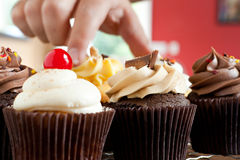 Hand Grabbing a Gourmet Cupcake Stock Photo