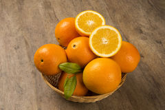 Close up of some oranges in a basket over a wooden surface Stock Photos
