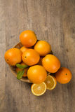 Close up of some oranges in a basket over a wooden surface. Fresh fruit royalty free stock photos