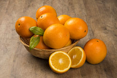 Close up of some oranges in a basket over a wooden surface. Fresh fruit royalty free stock image