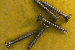 Detail of some screws. Close up of some screws, on a yellow background stock image