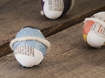 Close up of some trendy selfmade easter eggs. Three selfmade easter eggs sticked with newspaper on a wooden table (selective focus stock image