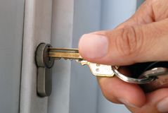 Put a key in a lock. Close-up of someone putting a key in a door lock stock image