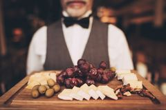 Close up. Sommelier is holding snacks for red wine on wooden plate. Grapes. Cheese. Olives. Walnut. Waiter with wooden tray royalty free stock photos