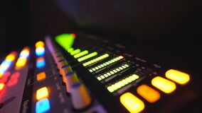 Close up of soundboard with knobs and green color equalizer in night club. View on audio waves or music control levels
