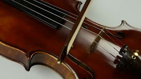Close up soundboard of violin and bow. The bow moves along the violin string. stock video footage