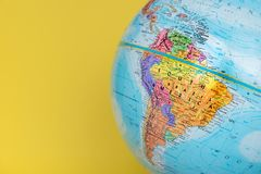 Close-up of South America on globe with solid yellow background stock image