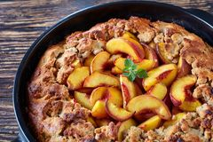 Close up of southern dessert peach cobbler. Close up of delicious southern dessert peach cobbler baked in a black dish, presented on old wooden table stock image