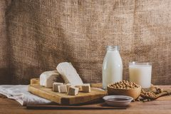Soy products such as, milk, tofu and sauce vintage. Close up of soybeans in wooden bowl on sackcloth background. Soy products such as, milk, tofu and sauce stock photography
