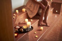 Close up of spa bath stuff on wooden tray. Concept of relaxation and body care. Close up photo of spa bath stuff on wooden tray while young woman sitting on royalty free stock photo