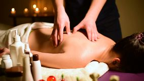 Close-up spa massage woman`s shoulders and back. Male hands do massage to a woman in a dark room with candles in the. Background stock footage