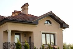 Close up of spacious brown shingle roof of modern luxurious expe. Nsive residential cottage house with three chimneys, big windows and gutters pipes Royalty Free Stock Photos