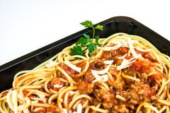 Close up of Spaghetti. Close-up of fresh Spaghetti decorated with a piece of parsley in a black take-out package Stock Images