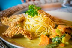 Close-up of spaghetti green curry with fried pork on table. royalty free stock photo
