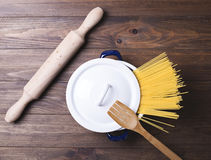 Close-up of spaghetti inside a pot next to a wooden fork and a roller on wooden table Royalty Free Stock Image