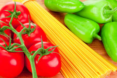 Close-up spaghetti pasta, ripe tomatoes and green peppers Royalty Free Stock Photos