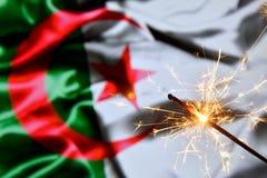Close up of sparkler burning over Algeria flag. Holidays, celebration, party concept. Close up of sparkler burning over Algeria flag. Holidays, celebration royalty free stock photos