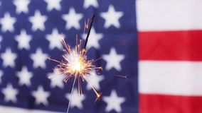 Close up of sparkler burning over american flag stock video