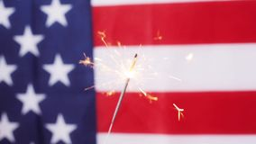 Close up of sparkler burning over american flag stock video footage