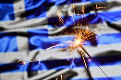Close up of sparkler burning over Greece, Greek flag. Holidays, celebration, party concept. Close up of sparkler burning over Greece, Greek flag. Holidays stock photo