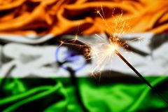 Close up of sparkler burning over India, Indian flag. Holidays, celebration, party concept. stock photos