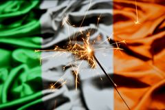 Close up of sparkler burning over Ireland, Irish flag. Holidays, celebration, party concept. Close up of sparkler burning over Ireland, Irish flag. Holidays royalty free stock images