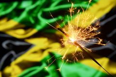 Close up of sparkler burning over Jamaica, Jamaican flag. Holidays, celebration, party concept. Close up of sparkler burning over Jamaica, Jamaican flag stock images
