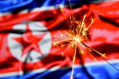 Close up of sparkler burning over North Korea, Korean flag. Holidays, celebration, party concept. Close up of sparkler burning over North Korea, Korean flag stock image