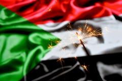 Close up of sparkler burning over Sudan flag. Holidays, celebration, party concept. stock photo