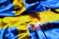 Close up of sparkler burning over Sweden, Swedish flag. Holidays, celebration, party concept. royalty free stock images