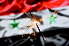 Close up of sparkler burning over Syria, Syrian flag. Holidays, celebration, party concept. stock images