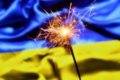 Close up of sparkler burning over Ukraine, Ukrainian flag. Holidays, celebration, party concept. stock photos