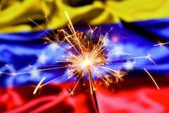 Close up of sparkler burning over Venezuela, Venezuelan flag. Holidays, celebration, party concept. royalty free stock photography