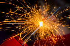 Close Up Of A Sparkler. Close up image of a sparkler burned halfway down with sparks flying all around Stock Photos