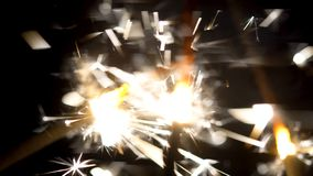Close-up of sparkling sparklers in dark. Little festive fire fireworks on sticks are brightly shinning in darkness. Holiday element stock photos