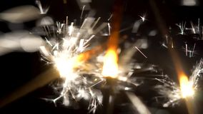 Close-up of sparkling sparklers in dark. Little festive fire fireworks on sticks are brightly shinning in darkness