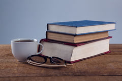 Spectacles, black coffee and book stack on wooden table. Close-up spectacles, black coffee and book stack on wooden table Stock Photos