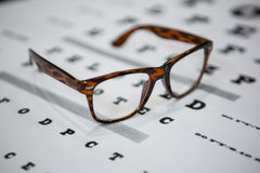 Close-up of spectacles on eye chart Royalty Free Stock Photo